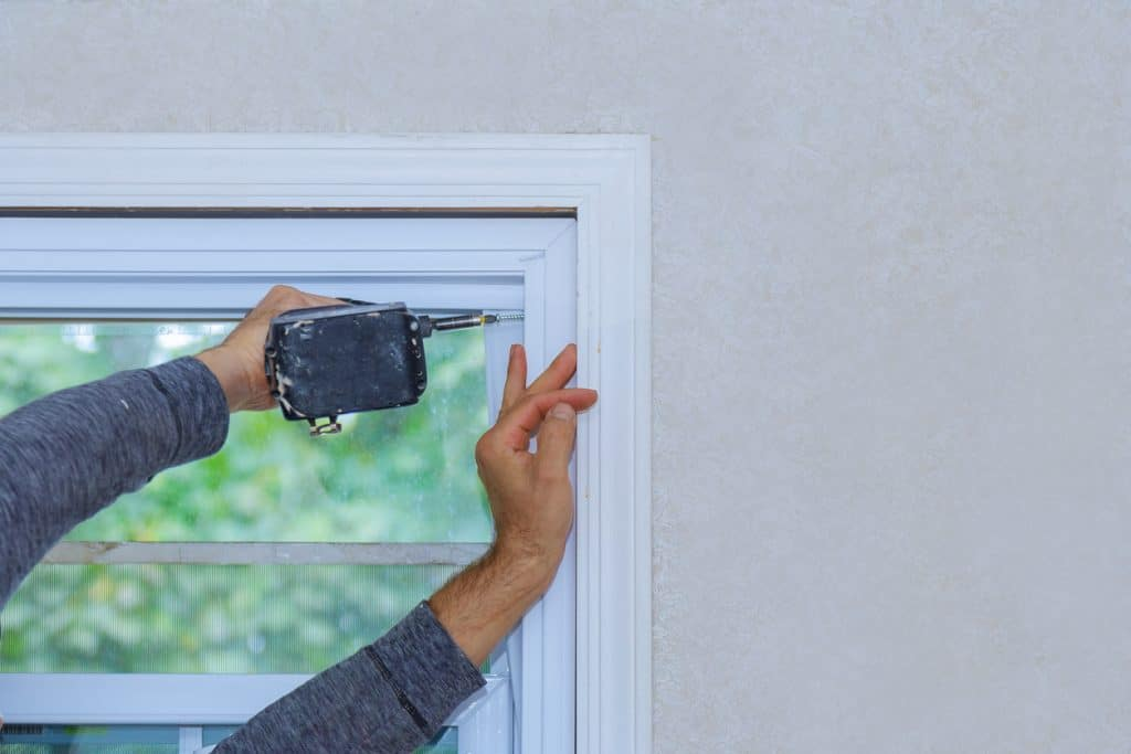 Construction worker installing window in house
