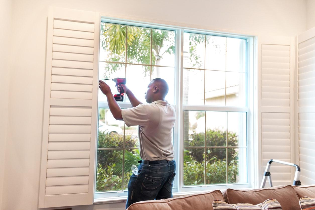 Window treatment installer installs wooden shutters RM