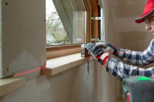 home improvement handyman installing window sill in new build attic by using leveler and laser leveler