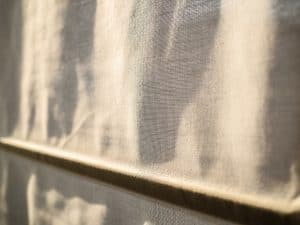 The Roman curtains close a window from the sunset sun. Warm lighting gets through a window