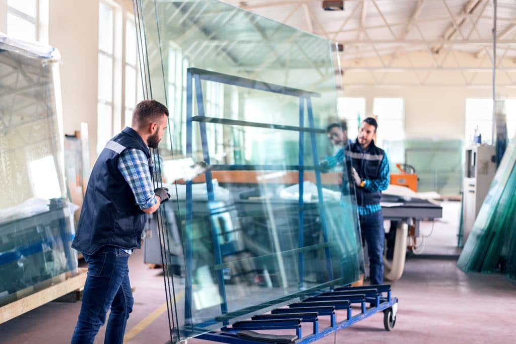 Workers packaging glass sheets in warehouse